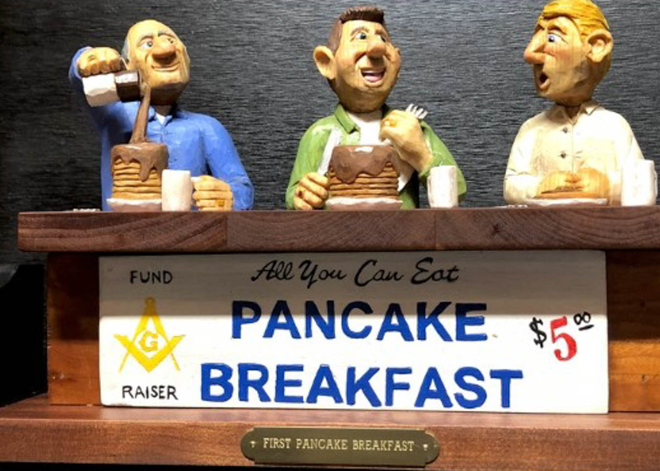 """3-D art of three men at table labeled, """"All You Can Eat Pancake Breakfast."""""""