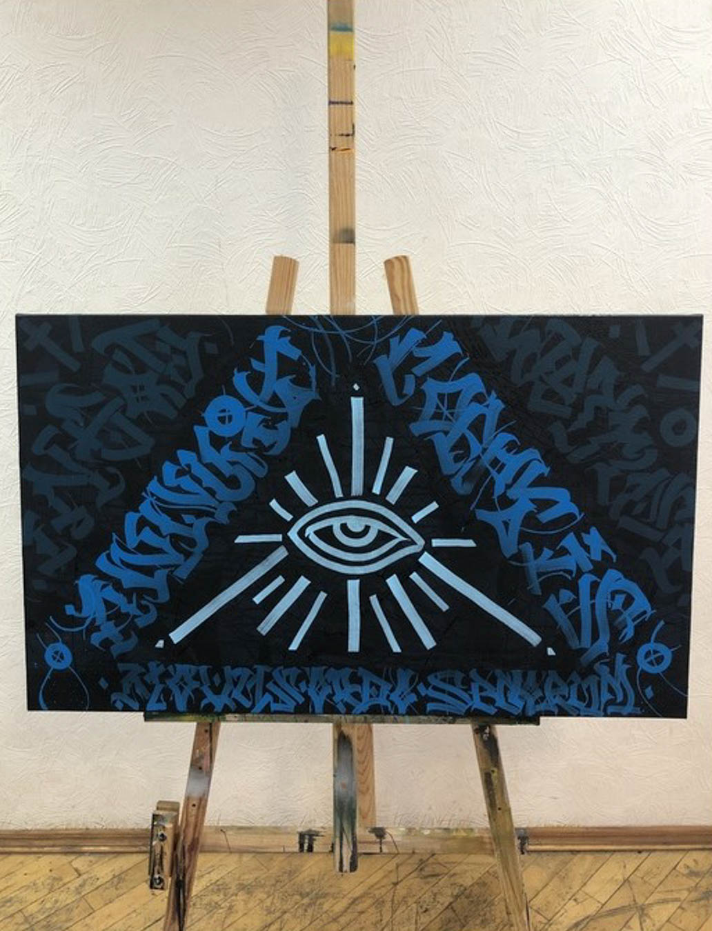 Print of eye surrounded by pyramid shape made of symbols.