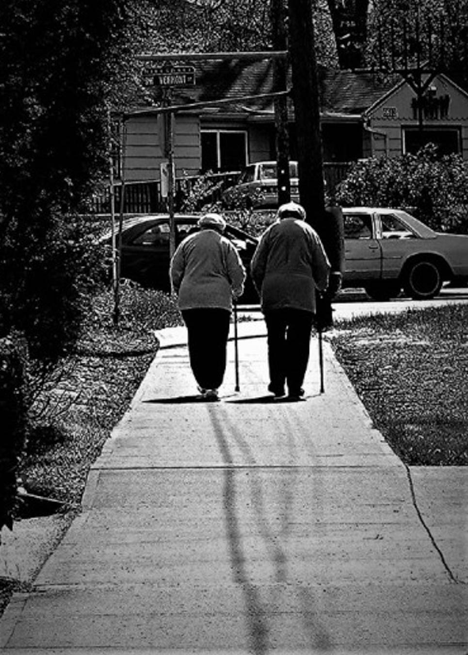 Black and white image of two elderly women walking together.
